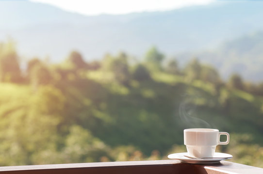 White cup of hot coffee on balcony with natural and mountains.