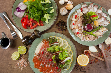 Different vegetables, meat, red fish and other dishes, sauces, snacks and spices on a wooden background