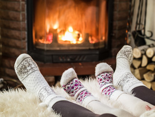 Warming and relaxing near fireplace. Woman and child feet in fro
