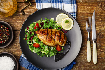Grilled chicken breast with green salad on a black plate.