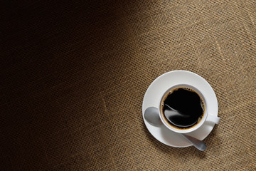 Top view of cup of coffee on burlap background