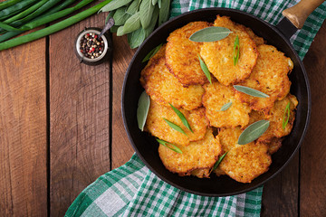 Fried potato pancakes in a frying pan on a wooden table. Top view