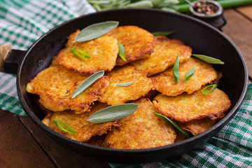 Fried potato pancakes in a frying pan on a wooden table