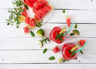 Fresh watermelon smoothies with lime and mint on white wooden background. Top view