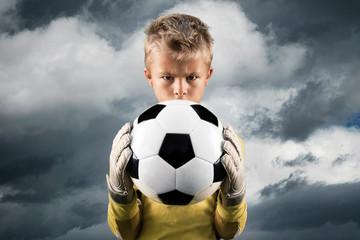 Aspiring young kid posing as a goal keeper.