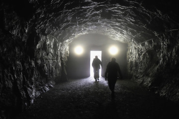Two persons walk to the light in the end of the tunnel.