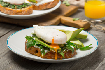 Poached egg on piece of bread with avocado and arugula