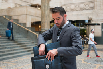 Businessman searching for something in his briefcase
