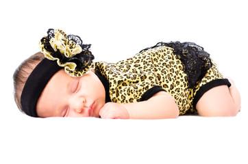 Cute sleeping newborn girl in a leopard clothes