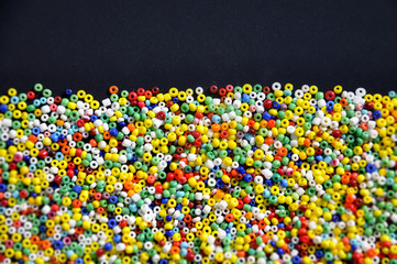 Multicolor beads on a dark surface with space for text at the top. Background, texture.