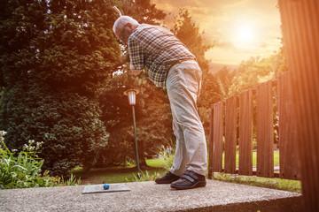 Minigolf in der Abendsonne.Ein Rentner steht am Abschlag und holt aus für einen weiten Schlag. Die Sonne steht ihm im Rücken.