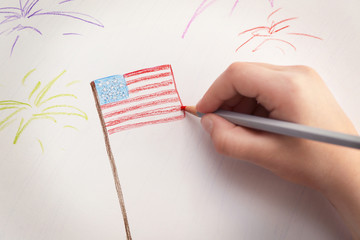 Child's hand drawing American flag on paper