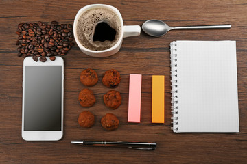 Cup of coffee, phone and notepad  on wooden background