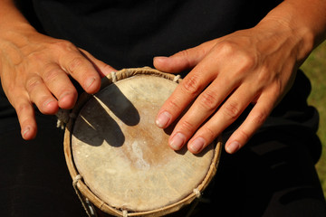 Close up of hands of a woman playing a drum