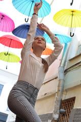 Girl posing under colorful umbrellas