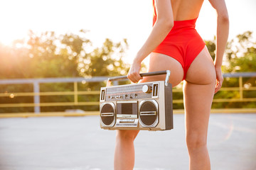 Back view of a roller girl holding old record player
