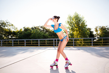 Woman in blue swimsuit riding on roller skates at park