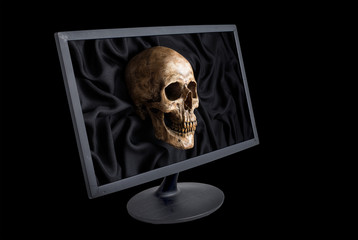 mix up of skull on black fabric and old computer monitor on black background in computer virus warning concept