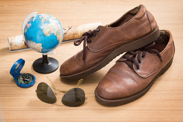 still life photography : brown leather shoes, sunglasses, compass, globe and map in traveler concept
