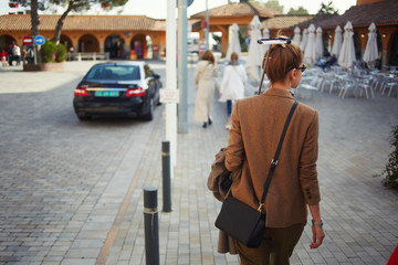 Rear view of stylish young woman holding monopod stick with smart phone walking in new city