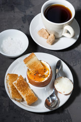 boiled egg, cup of coffee and crispy bread, top view