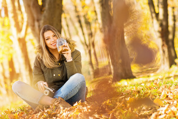 Young blonde woman drinking coffee outdoors in park on sunny autumn day