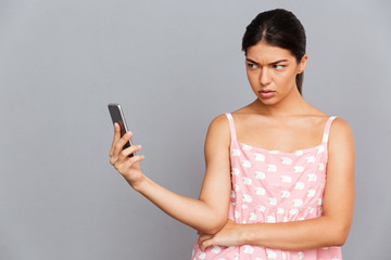 Displeased woman in pink dress making selfie photo on smartphone