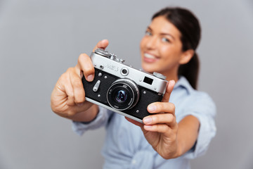 Young beautiful smiling brunette woman showing photo camera