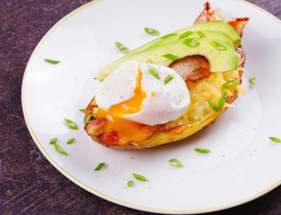 Stuffed potato with bacon, poached egg, avocado, cheese and spring onion