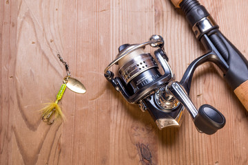 fishing rod and lure on wood surface