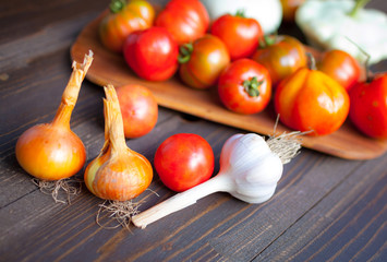 Red tomatoes, squash, onions and garlic on a wooden table. Vegetables.
