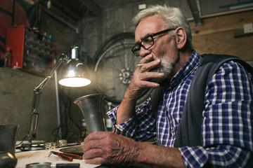 Smoking senior man inspecting antique tin vase.