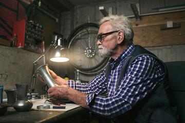 Senior man looking at antique tin vase.