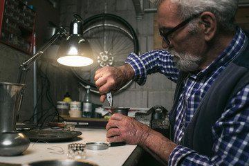 Man fixing antique vase with pincers