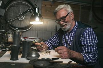 Smiling senior man soldering metal rings