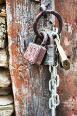 Vintage Corroded Padlocks  with Chain on a Ancient Red Gate Background. Old Rusty Padlocks on a Wooden Door.