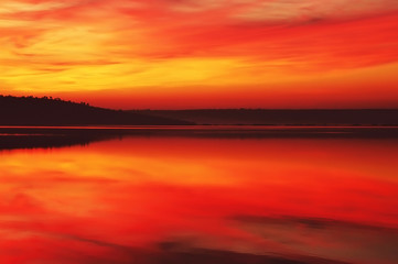 Keuken foto achterwand Rood beautiful sunset red and orange above the water surface of the lake. hilly shore away with silhouettes of trees. anyone.