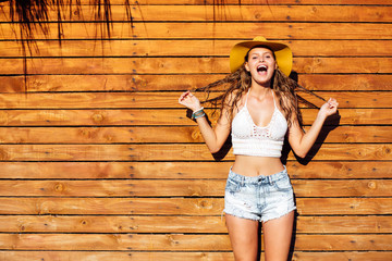 Sexy woman with short jeans pants standing on wooden wall