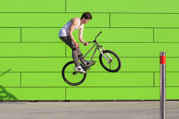 Boy on bike make the barspin trick at green wall background