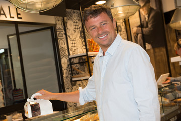 Man buying some cookies and cakes in a pastry shop