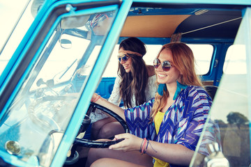 smiling young hippie women driving minivan car