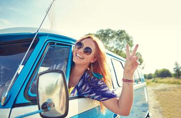 smiling young hippie woman driving minivan car
