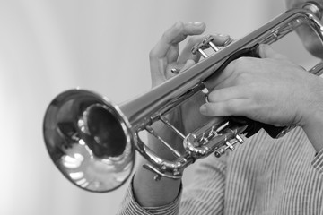 Hands of the musician playing a trumpet closeup in black and white