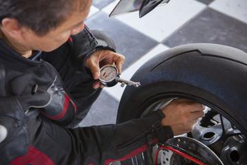 biker checking air pressure in rear wheel of big motorcycle