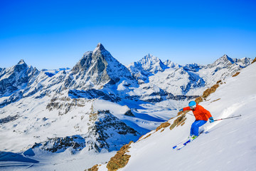 Wall Mural - Full length of turn man skiing on fresh powder snow with Matterhorn in background in Swiss Alps.