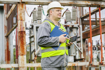 Electrician using tablet PC in electrical substation