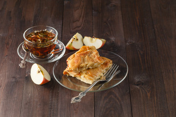 Apple pie on wooden table with tea