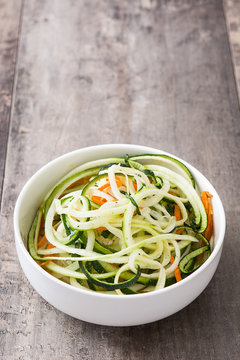 Carrot and zucchini noodles on wooden table