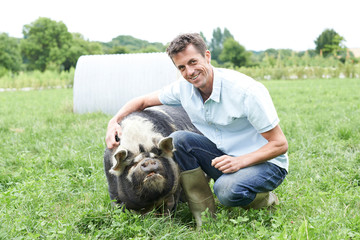 Portrait Of Farmer In Field With Pig