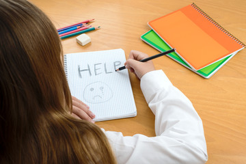 child abuse. A Horizontal image /poster covering the Social Issues of child abuse, by a schoolchild sat at a desk asking for help by a written message saying Help with a sad face .